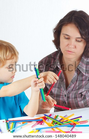 Young mother teaches her son to draw with color pencils on a white background - stock photo
