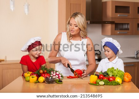 Young mother teaching children how to prepare salad. boy and girl learning to cook food at kitchen - stock photo