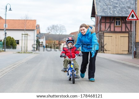Young mother teaching her 3 years old little son to ride a bike, outdoors - stock photo