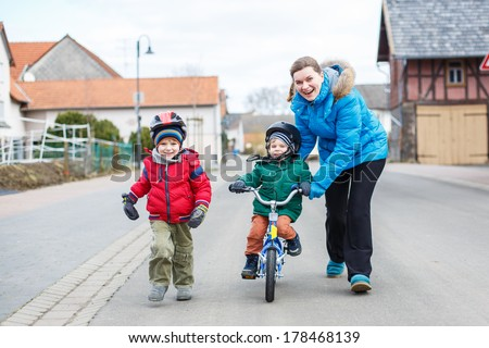Young mother teaching her 2 years old little son to ride a bike, outdoors. Another little boy running beside. - stock photo