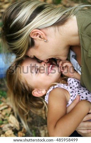 Young mother touching with nose her  daughter and both smiling.Little girl lying on mother lap. Focus is on blonde woman.