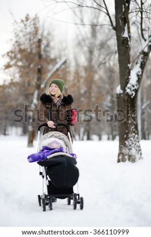 Young mother walking with baby in stroller and drinking hot coffee in winter park   - stock photo