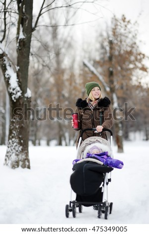 Young mother walking with baby in stroller and drinking hot coffee in winter park