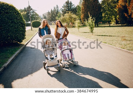 young mother walking with her baby and carries it in a beautiful pram - stock photo
