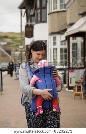 Young mother walking with her baby in a sling. - stock photo