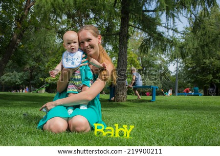Young mother walking with her baby in the park - stock photo