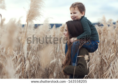 Young mother walking with her little son outdoors in autumn - stock photo