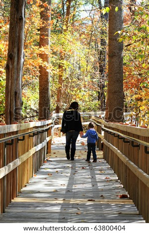 Young mother walking with little girl in a beautiful autumn park. - stock photo