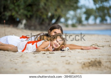 young mother wHappy young mother with a small daughter resting on the beachith a child on the beach