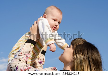 young mother with a baby on the sky background - stock photo