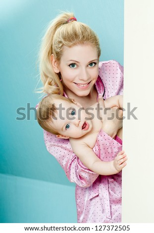 young mother with a charming baby. indoors. - stock photo