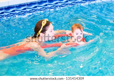Young mother with a little baby in the swimming pool - stock photo