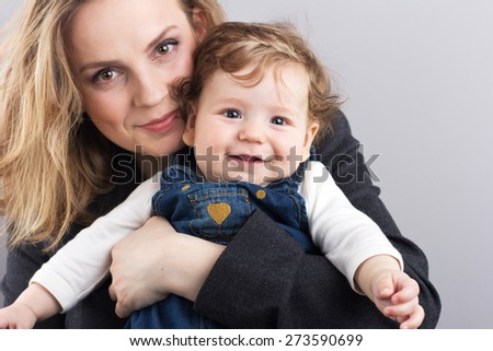 young mother with a little boy in her arms. Portrait of mother and son. Beautiful blonde. pectoral baby. happy family - stock photo