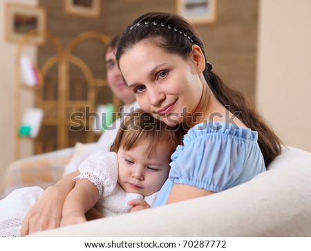 young mother with a little daughter together at home - stock photo