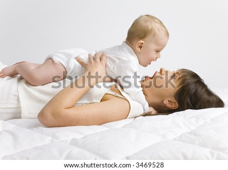 Young mother with baby boy. Lying on bed and hugging, having good fun. Side view