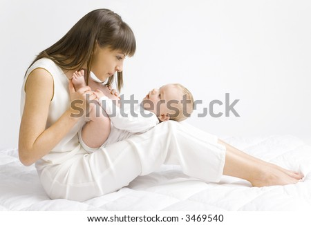 Young mother with baby boy. Sitting on white cloth and having fun. Whole bodys, side view - stock photo