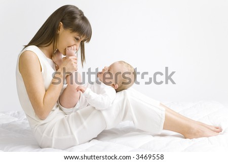Young mother with baby boy. Sitting on white cloth and having fun. Whole bodys, side view