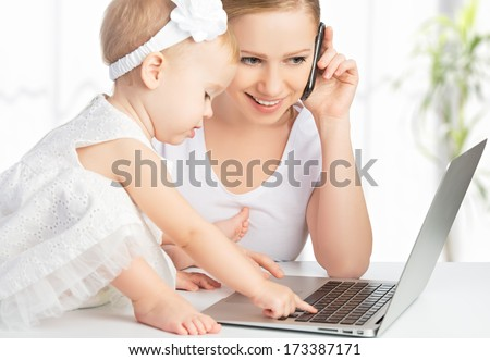 young mother with baby daughter works on the Internet with a computer and phone - stock photo