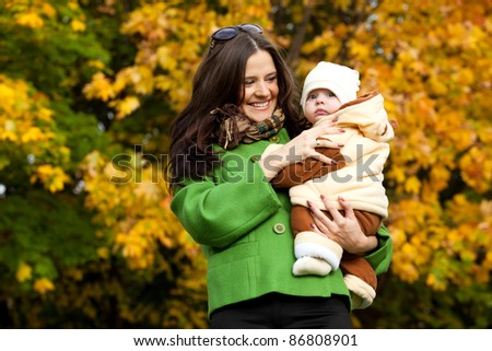 young mother with baby in arms up in fall city park - stock photo