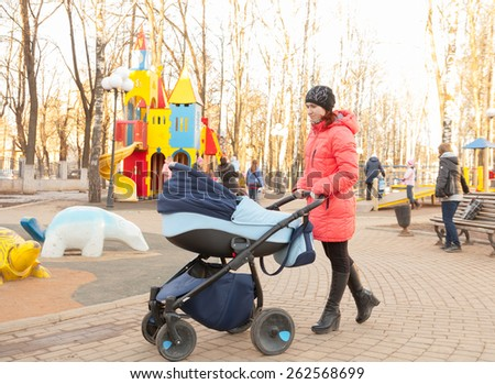 young mother with baby in stroller walking in   park.  - stock photo