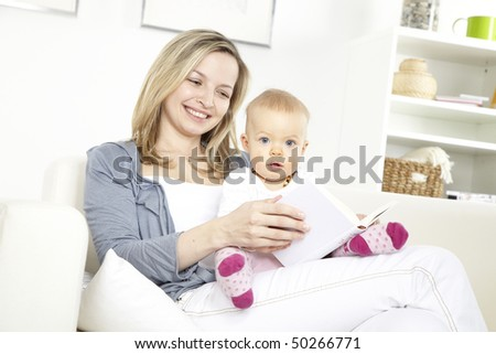 young mother with baby on a white sofa