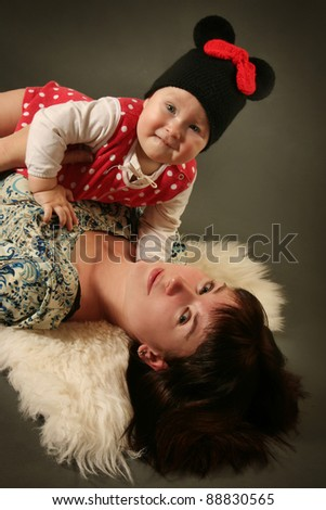 young mother with baby on grey background - stock photo