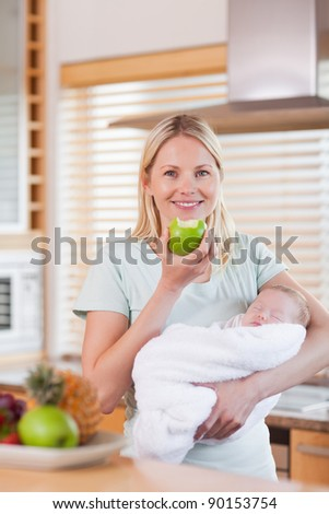 Young mother with baby on her arms having an apple - stock photo
