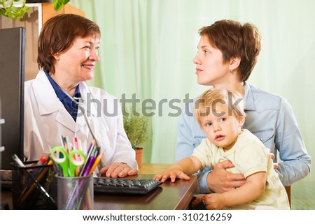 Young mother with baby talking with friendly pediatrician doctor at clinic office