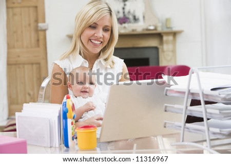 Young mother with baby working from home office - stock photo
