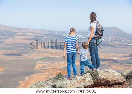 Young mother with backpack and her chid standing on cliff's edge and looking to a sky - stock photo