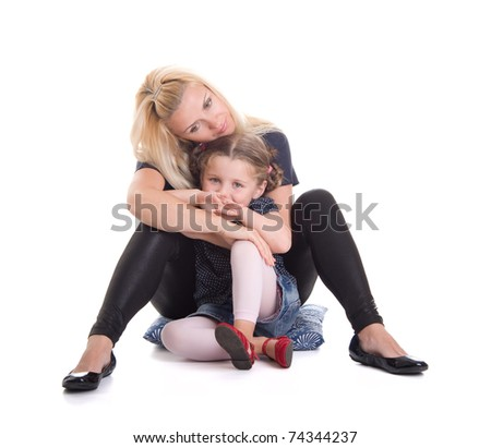 Young mother with beautiful daughter sitting in an embrace on white background - stock photo