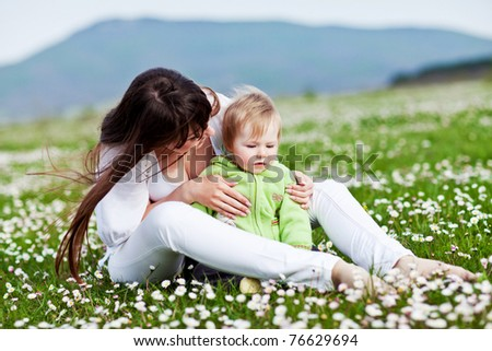 Young mother with child outside on a summer day. - stock photo