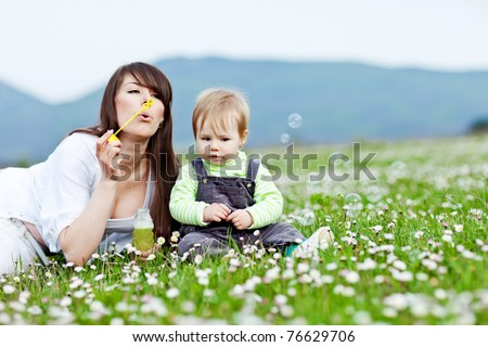 Young mother with child outside on a summer day.