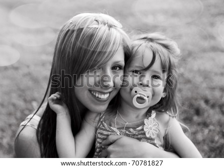 Young mother with child outside on a summer day.Black and white - stock photo