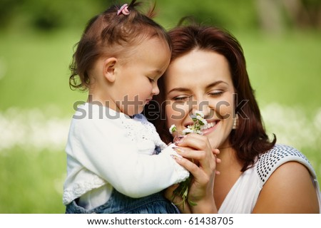 Young mother with child outside on a summer day. Focus is on the girl. - stock photo
