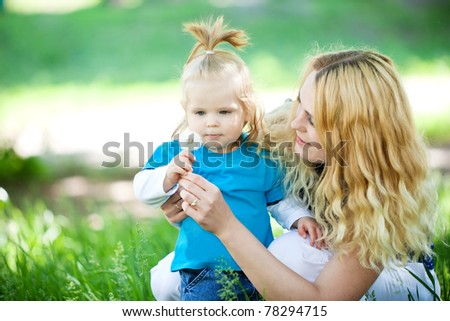 Young Mother With Child Playing Outside On A Summer Day