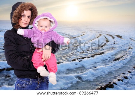 Young mother with cute baby dressed in a fur in winter cold weather. Seasonal fashion shot.