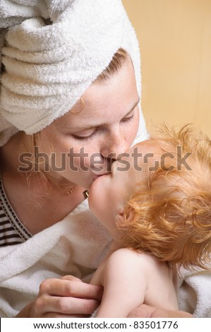 Young mother with cute little baby after bath