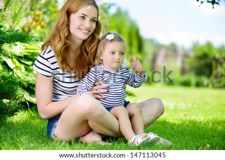 Young mother with cute little daughter at park on green grass