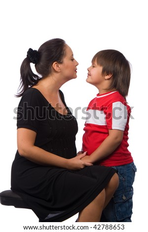 young mother with dark hair in a black dress talking with his son