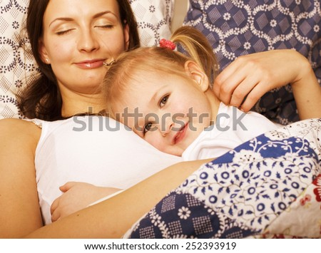 young mother with daughter at home playing, happy family close up in bed - stock photo