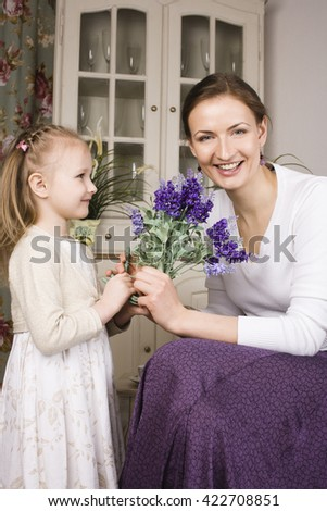 young mother with daughter at luxury home holding flowers smiling, gift for mummy, lifestyle people concept - stock photo