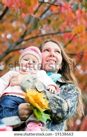 Young mother with daughter enjoying beautiful autumn day. Focus on baby