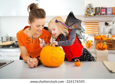 Young mother with daughter in bat costume creating big orange pumpkin Jack-O-Lantern on Halloween party in decorated kitchen. Traditional autumn holiday - stock photo