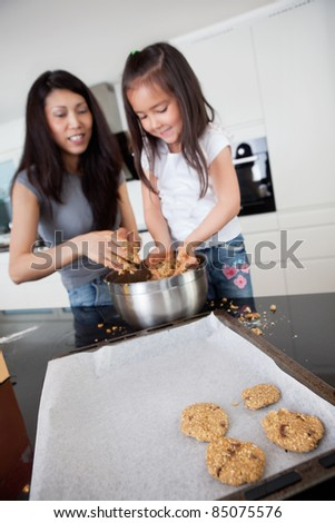 Young mother with daughter in kitchen preparing cookies - stock photo