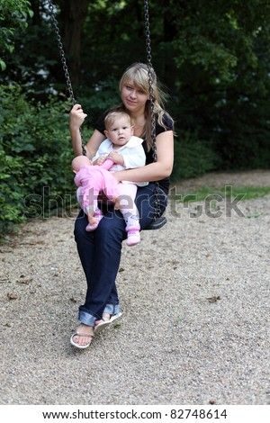 Young mother with daugther on swing - stock photo