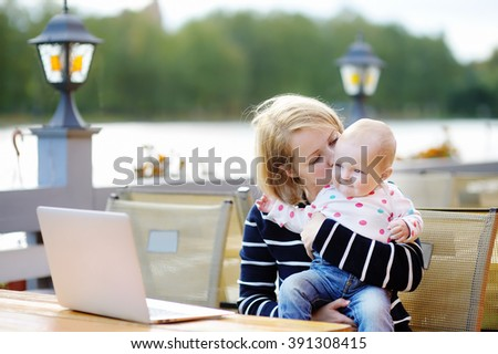 Young mother with her adorable baby girl working or studying on her laptop in outdoor cafe  - stock photo