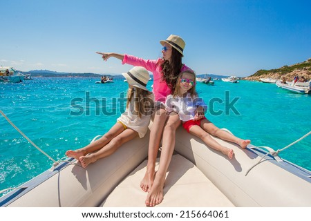 Young mother with her adorable baby girls resting on a big boat - stock photo