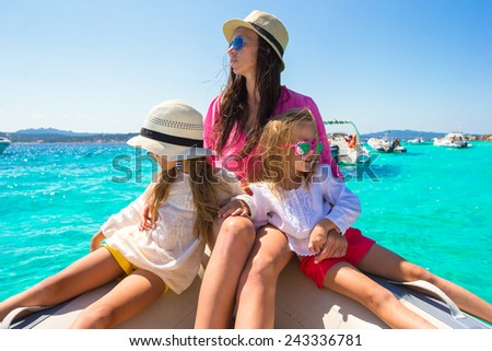 Young mother with her adorable little girls resting on a big boat - stock photo