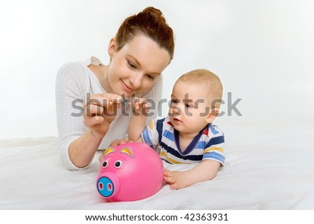 young mother with her adorable newborn baby and a piggy bank - stock photo